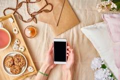 Le mani delle donne di Flatlay che tengono uno smartphone Resto domestico accogliente, vacanza, fine settimana Ragazza che si tro fotografie stock