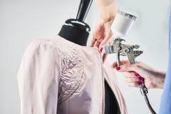 Le mani delle donne effettuano il processo di verniciatura del bomber sul manichino Fotografia Stock Libera da Diritti