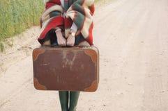 Le mani delle donne giudicano la vecchia valigia all'autunno all'aperto sul paese Immagini Stock