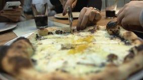 Le mani delle donne hanno tagliato la fetta di pizza calda con il rullo-coltello in pizzeria stock footage