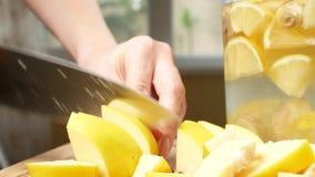 Le mani delle donne incidono i pezzi di cotogna per una bevanda fatta dall'agrume fatto a mano con lo zenzero 4k, archivi video