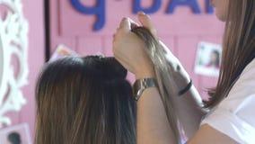Le mani delle donne intrecciano i capelli con un elastico archivi video