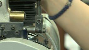Le mani delle donne mettono il materiale che è pulito su una macchina industriale stock footage