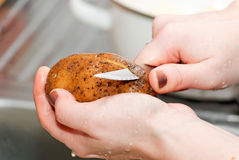 Le mani delle donne puliscono le patate Immagine Stock