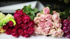 Le mani delle donne sono messe un mazzo delle rose rosse alla stanza frontale di negozio stock footage