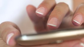 Le mani delle donne tengono lo smartphone ed il browser il sito Web ed il email Primo piano La mano di una ragazza sta scrivendo  archivi video