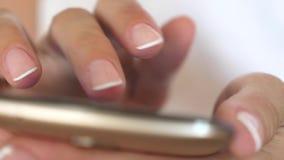 Le mani delle donne tengono lo smartphone ed il browser il sito Web ed il email Primo piano La mano di una ragazza sta scrivendo  stock footage