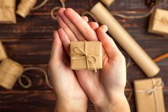 Le mani delle donne tengono un regalo della carta del mestiere Contro lo sfondo dell'arancia secca, cannella, pigne, anice su una fotografia stock