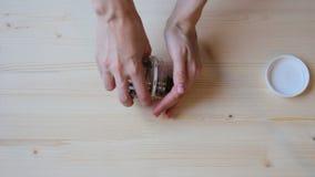 Le mani delle donne versano fuori le monete dal barattolo alla tavola di legno archivi video
