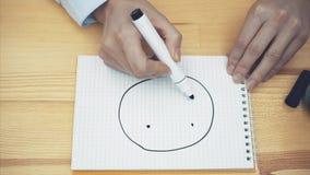 Le mani delle giovani donne sulla tavola La mano della donna su uno strato bianco con un indicatore nero dipinge un sorriso Il co archivi video