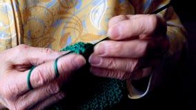 Le mani delle nonne lavorano all'uncinetto il filato verde Clip del primo piano di funzionamento senior della donna video d archivio