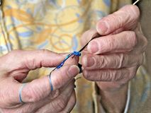 Le mani delle nonne lavorano all'uncinetto il filo blu Clip del primo piano del lavoro all'uncinetto senior della donna fotografia stock libera da diritti