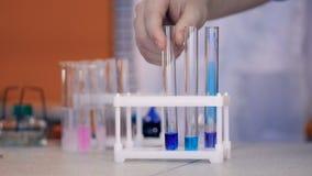 Le mani dello scolaro aggiungono i reagenti chimici nella fiala, provetta in laboratorio Primo piano archivi video
