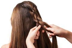 Le mani dello stilista tesse i capelli lunghi e serici, isolati fotografia stock libera da diritti