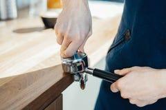 Le mani di barista che tengono il portafilter ed il caffè manomettono producendo un caffè del caffè espresso fotografia stock