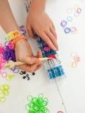 Le mani di Childs con la banda tessono, gancio del croche e elast multicoloured Immagini Stock Libere da Diritti