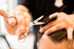 Le mani di giovane barbiere che fanno taglio di capelli al cliente attraente fotografie stock libere da diritti