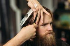 Le mani di giovane barbiere che fanno taglio di capelli all'uomo barbuto attraente in parrucchiere immagini stock