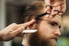 Le mani di giovane barbiere che fanno taglio di capelli all'uomo barbuto attraente in parrucchiere immagine stock libera da diritti