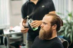 Le mani di giovane barbiere che fanno taglio di capelli all'uomo barbuto attraente in parrucchiere fotografia stock