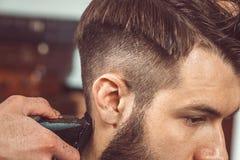 Le mani di giovane barbiere che fanno taglio di capelli all'uomo attraente in parrucchiere immagini stock libere da diritti