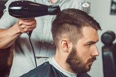 Le mani di giovane barbiere che fanno taglio di capelli all'uomo attraente in parrucchiere Fotografie Stock Libere da Diritti