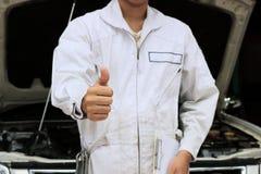 Le mani di giovane meccanico professionista equipaggiano la mostra del pollice su come segno di successo con l'automobile in capp fotografia stock