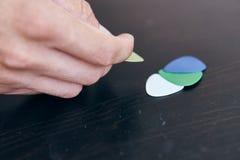 Le mani, di mediatori colorati multi per la chitarra si trovano sulla tavola Immagine Stock