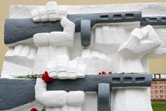 Le mani di pietra bianche tengono i distributori automatici con i fiori, un monumento immagini stock