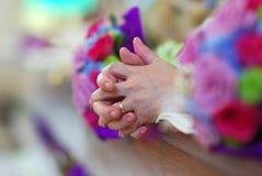 Le mani di preghiera a si alterano durante la cerimonia nuziale della chiesa Fotografia Stock