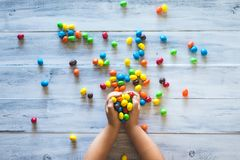 Le mani di un bambino che tengono mucchio delle caramelle variopinte fotografia stock