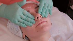 Le mani di un estetista in crema di nutrizione d'idratazione di Yunanosyut dei guanti verdi sulla pelle del fronte di una donna L