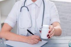 Le mani di un medico della ragazza in uniforme si siede allo scrittorio e tiene un barattolo con una droga immagini stock