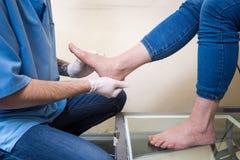 Le mani di un ortopedico di medico del giovane conduce i sistemi diagnostici, prova del piede di piede di una donna, per la fabbr Immagini Stock