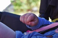 Le mani di un pugno del bambino, fuoco selettivo, il bambino è nel passeggiatore fotografia stock