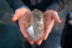 Le mani di un uomo che tiene un grande, cristallo di quarzo leggero sembra potenti immagini stock