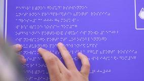 Le mani di un uomo cieco in una camicia che indica una fonte di Braille su una costruzione firmano stock footage