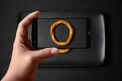 Le mani di un uomo prende le foto di alimento sulla tavola con il telefono Bagel su una banda nera Anello asciutto del pane, crac immagine stock