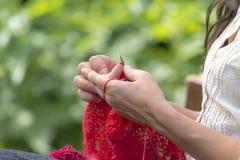 Le mani di una donna che lavora all'uncinetto con lana rossa/tricotta fotografie stock libere da diritti
