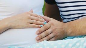 Le mani di una donna incinta e della sua tenuta del marito si gonfiano archivi video