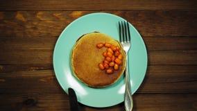 Le mani di vista superiore hanno messo il piatto con i pancake e le bacche sulla tavola di legno, carrello sparato stock footage