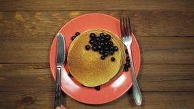 Le mani di vista superiore hanno messo il piatto con i pancake e le bacche sulla tavola di legno, carrello sparato archivi video