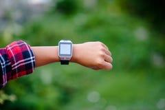 Le mani e gli orologi digitali dei ragazzi guardano il tempo nel polso T immagini stock libere da diritti