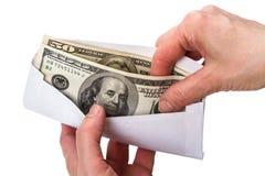 Le mani e la busta con incassano i dollari Fotografia Stock