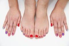 Le mani e le gambe delle donne con chiodi colorati immagine stock libera da diritti