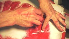 Le mani estraggono il primo piano delle lettere di rosso stock footage