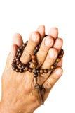 Le mani fanno attenzione a binded dal rosario di legno Immagine Stock