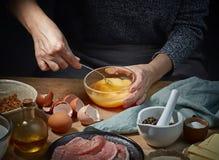 Le mani femminili è uova pungenti Fotografia Stock