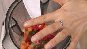 Le mani femminili aggiungono il peperoncino rosso piccante nel miscelatore per cucinare la salsa di verdure Vista superiore, vega archivi video