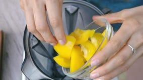 Le mani femminili aggiungono il peperone dolce giallo nel miscelatore per cucinare la salsa di verdure Vista superiore, vegano ed stock footage